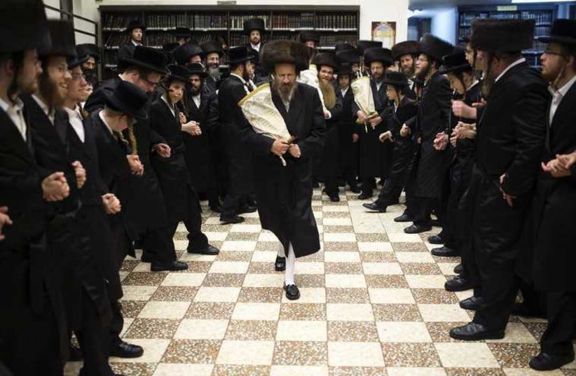Ultra-Orthodox Jews dance with Torah scrolls during the celebrations of Simchat Torah in a synagogue in the Mea Shearim neighborhood of Jerusalem (photo credit: REUTERS)
