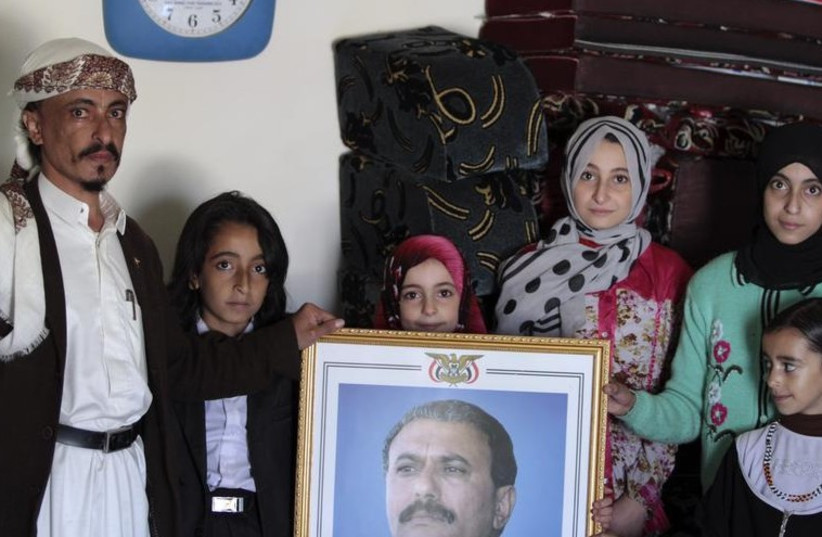 Chief rabbi of the Jews in Yemen Yahya Yosef Mosa with his family carries a picture of the ousted president of Yemen Ali Abdullah Salehin in his home in Sanaa (photo credit: REUTERS)