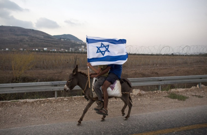 Jewish youths hold an Israeli flag as they ride a donkey during a rally march outside the West Bank settlement of Itamar, near Nablus (photo credit: REUTERS)