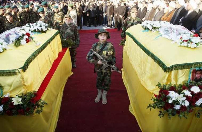 The son of Hezbollah operative Abbas Hijazi, who died in an airstrike in Quneitra, carries a toy weapon as he stands between his father's (R) and grandfather's (L) coffins in Ghaziyeh village (photo credit: REUTERS)
