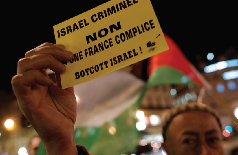 A PALESTINIAN supporter holds a protest leaflet advocating a boycott of Israel in France (photo credit: REUTERS)