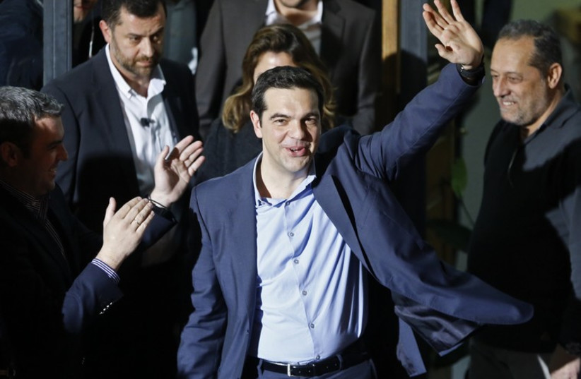 The head of radical leftist Syriza coalition, Alexis Tsipras, waves while leaving the party headquarters after winning the elections in Athens. (photo credit: REUTERS)