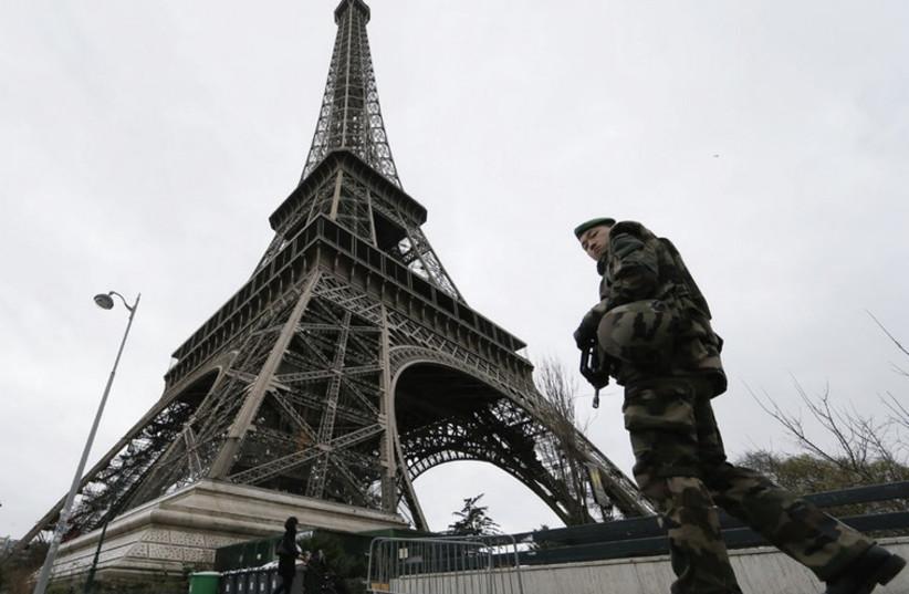 A soldier patrols alongside the Eiffel Tower. (photo credit: GONZALO FUENTES / REUTERS)
