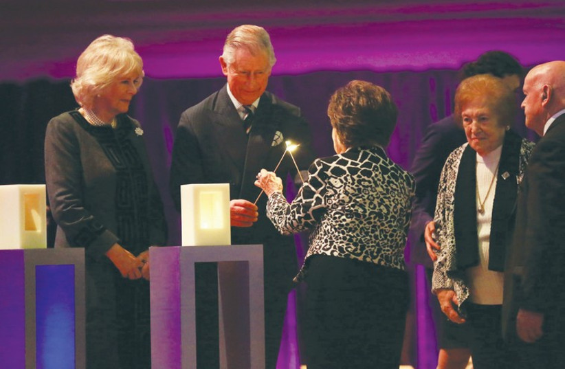 PRINCE CHARLES and a Holocaust survivor light a candle at Central Hall Westminster, as his wife, Camilla, looks on. (photo credit: Courtesy)