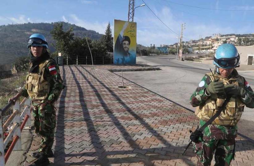 UNIFIL members beside a banner for Hezbollah leader Sayyed Hassan Nasrallah in south Lebanon  (photo credit: REUTERS)