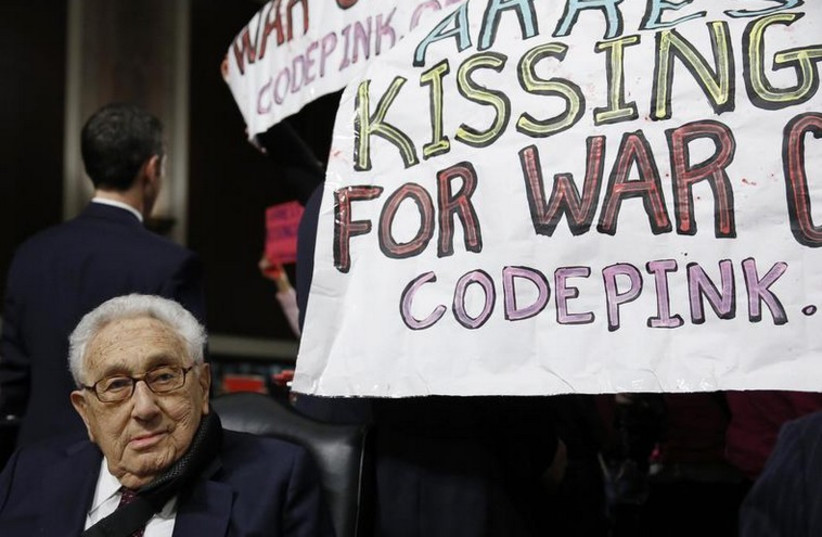 Former United States Secretary of State Henry Kissinger sits calmly as Code Pink demonstrators demand his arrest (photo credit: REUTERS)