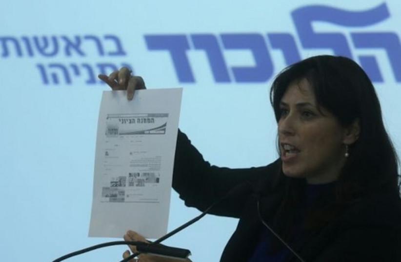Hotovely holds up screenshot of Labor website with V15 link. (photo credit: MARC ISRAEL SELLEM/THE JERUSALEM POST)