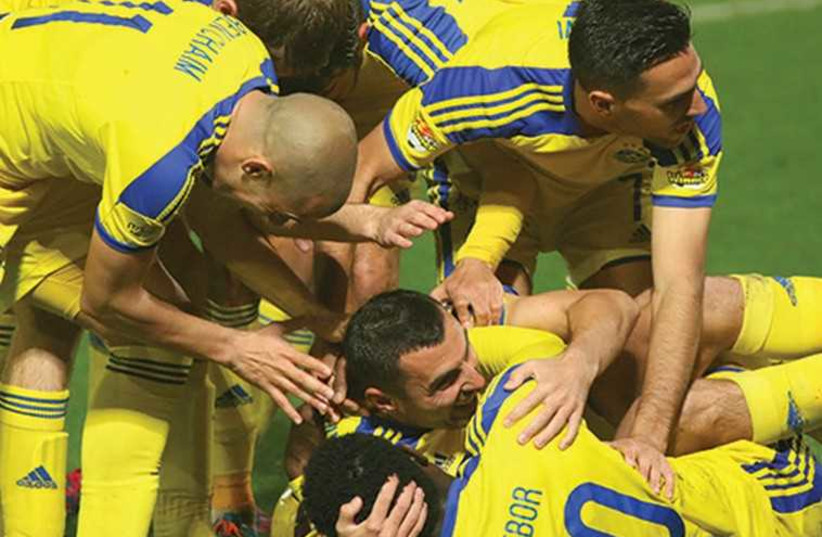 Maccabi Tel Aviv players celebrate with Nikola Mitrovic after he scored the team's second goal in last night's 2-0 win over Hapoel Tel Aviv in the derby at Bloomfield Stadium. (photo credit: ADI AVISHAI)
