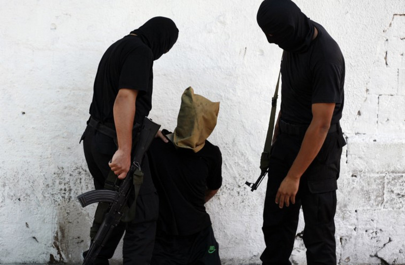 A Hamas militant grabs a Palestinian suspected of collaborating with Israel, before being executed in Gaza City August 22, 2014. (photo credit: REUTERS)