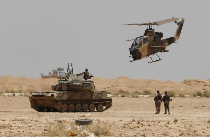 Jordanian military helicopter flies over an armored vehicle near the Karameh border crossing on the Jordanian-Iraqi border (photo credit: REUTERS)