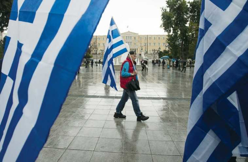 A man holding a Greek flag walks on central Syntagma square in Athens. (photo credit: REUTERS)