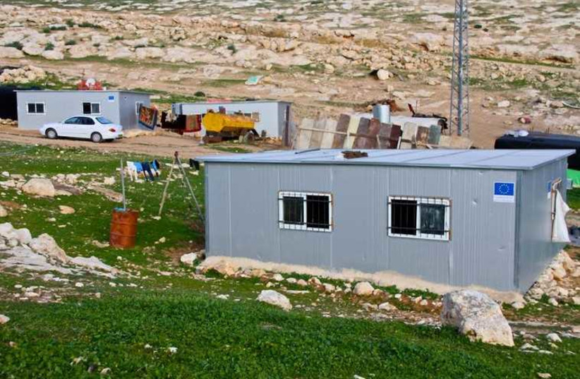 The blue EU logo seen on new modular structures in an illegal Beduin encampment in the Judean hills outside the Ma'alen Adumim settlement.  (photo credit: TOVAH LAZAROFF)