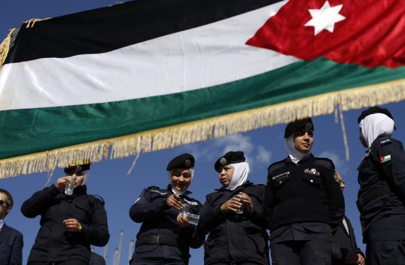 Jordanian police women stand guard near a Jordanian national flag during a rally in loyalty to the King and against the Islamic State (photo credit: REUTERS)