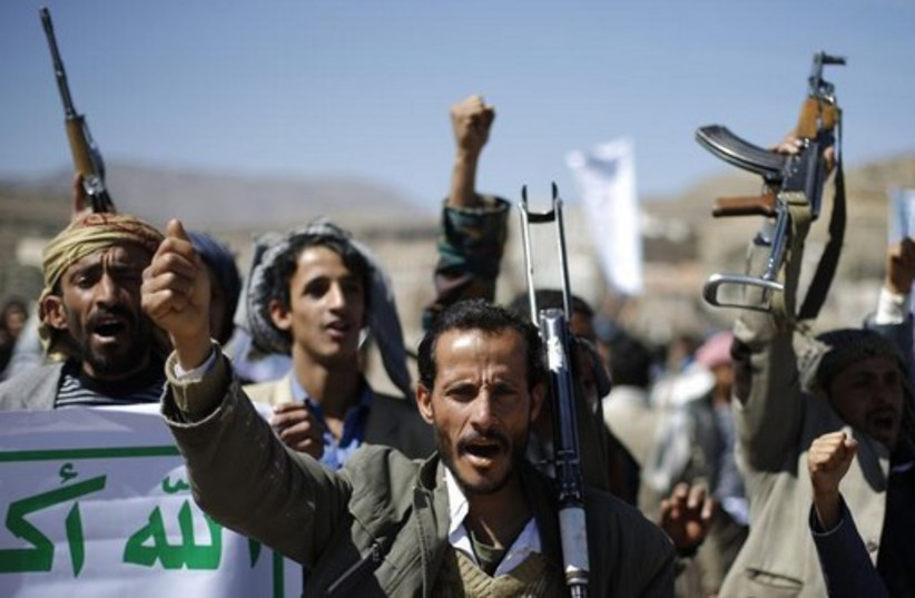 Followers of the Houthi movement shout slogans during a gathering to show support to the movement outside the Presidential Palace in Sanaa (photo credit: REUTERS)