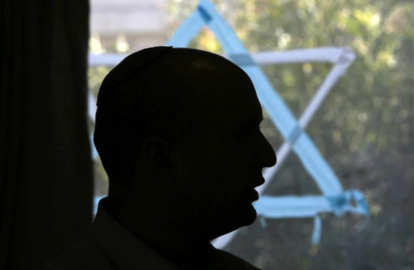 Naftali Bennett, head of the Bayit Yehudi party, is silhouetted as he talks to students at a pre-army training course as he campaigns in the Shapira Center near the southern city of Ashkelon (photo credit: REUTERS)