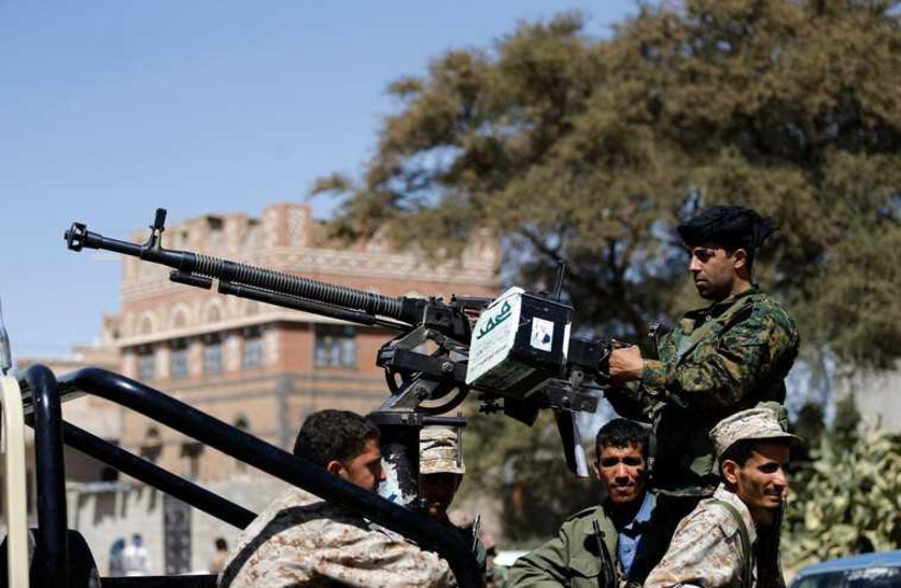 Houthi fighters ride a patrol truck in Sanaa (photo credit: REUTERS)