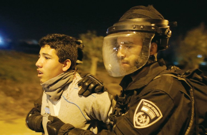 Police detain an Arab youth during clashes in the southern town of Rahat on January 20. (photo credit: REUTERS)