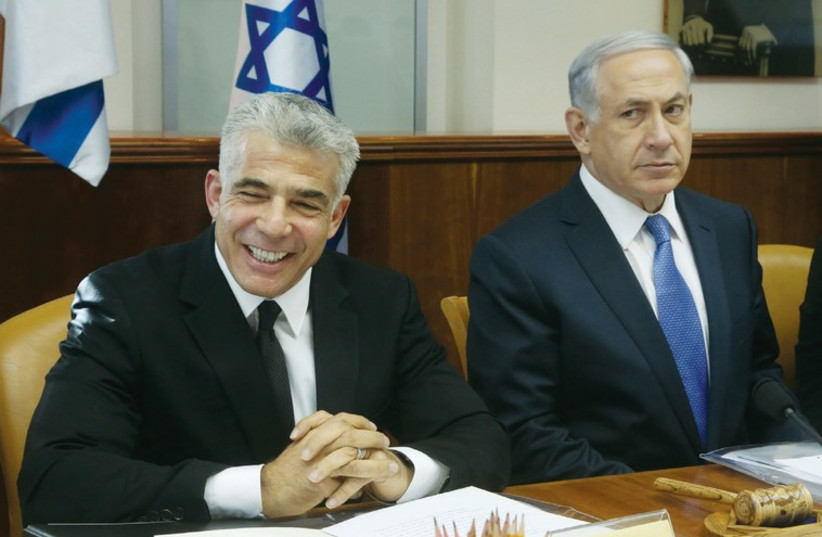 Netanyahu and Lapid at a cabinet meeting in October 2014. (photo credit: MARC ISRAEL SELLEM/THE JERUSALEM POST)