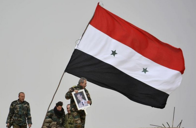 A fighter loyal to Syria's president Bashar Assad holds his picture as fellow fighters rest by a Syrian national flag after gaining control of the area in Deir al-Adas, a town south of Damascus (photo credit: REUTERS)