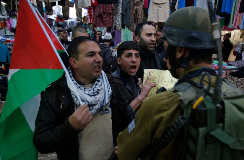 Palestinian protesters argue with an IDF soldier during a protest against the visit of President Reuven Rivlin to Hebron (photo credit: REUTERS)