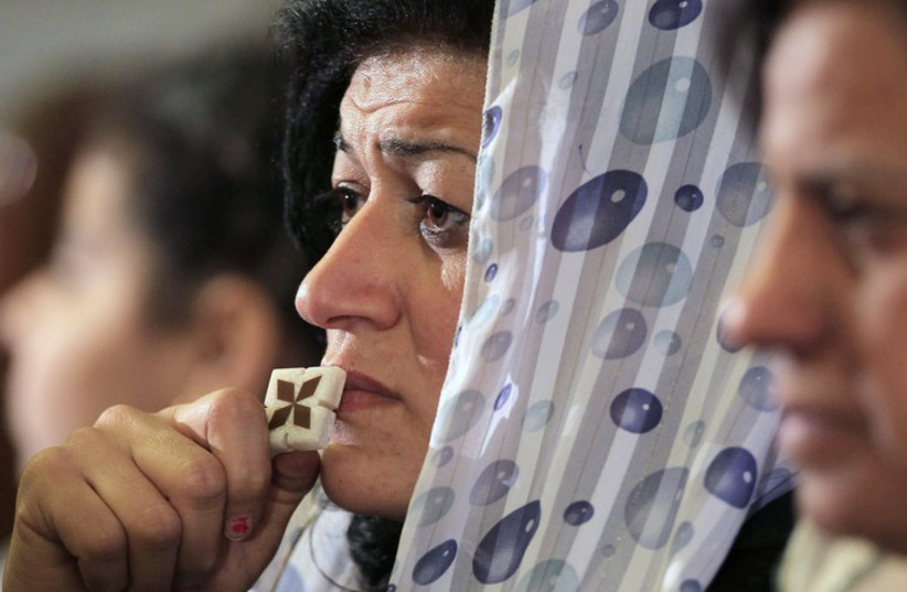 A Coptic Christian attends the Coptic mass prayers for the Egyptians beheaded in Libya, at Saint Mark's Coptic Orthodox Cathedral in Cairo. (photo credit: REUTERS)