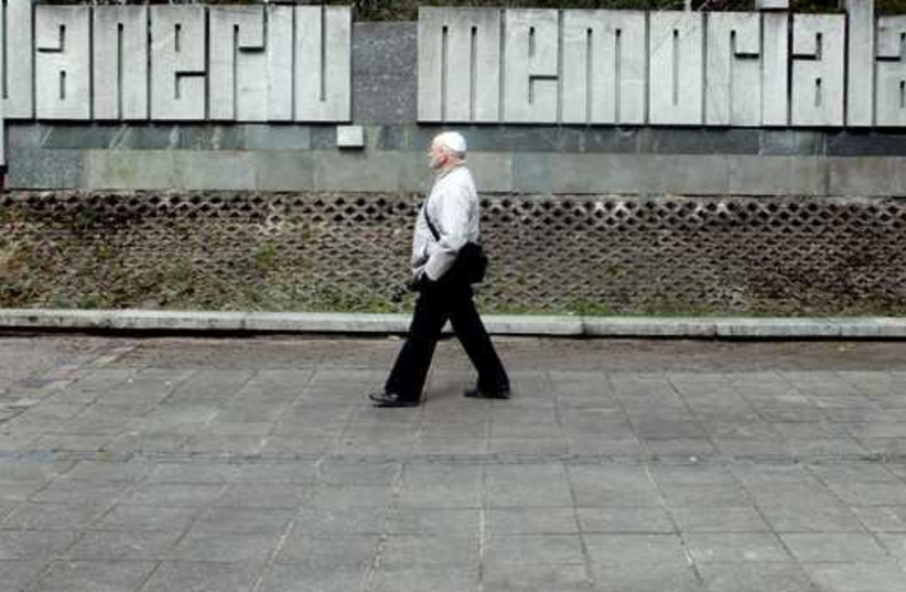 A man walks past a sign at a commemoration place during the March of the Living to honor Holocaust victims in Paneriai near Vilnius, Lithuania (photo credit: REUTERS)