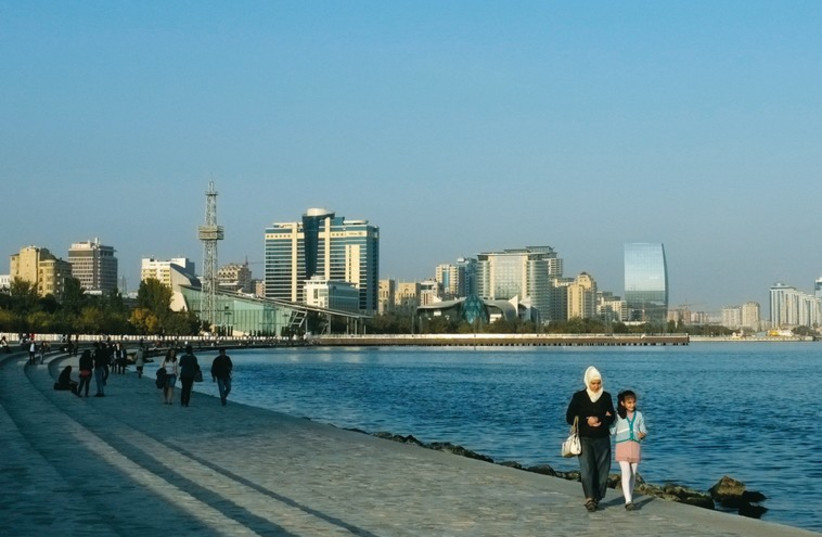 People walk along a seafront, with high-rise residential and commercial buildings in the background, in Baku on October 13, 2013. (photo credit: REUTERS)