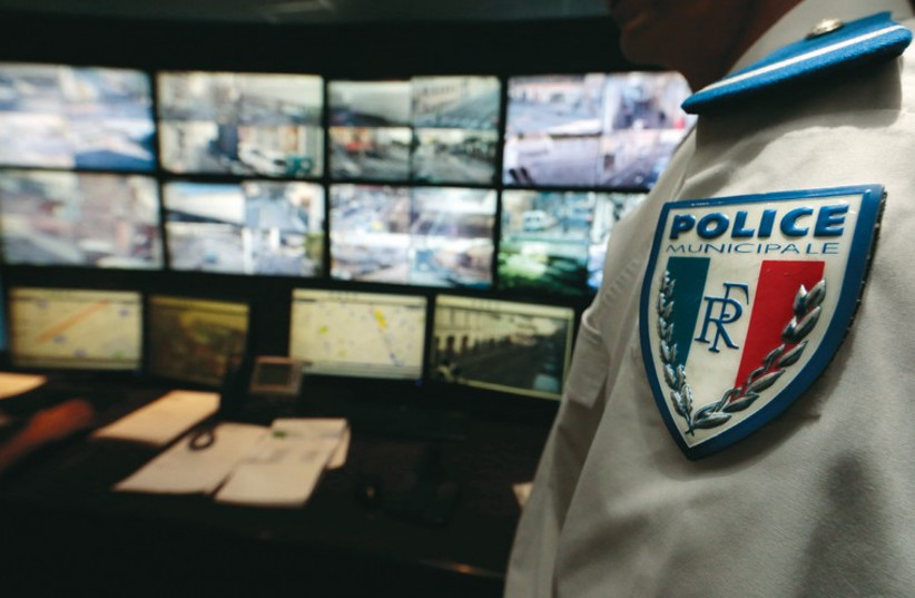 A municipal police officer in Nice watches screens in the video surveillance control room on February 9. (photo credit: REUTERS)