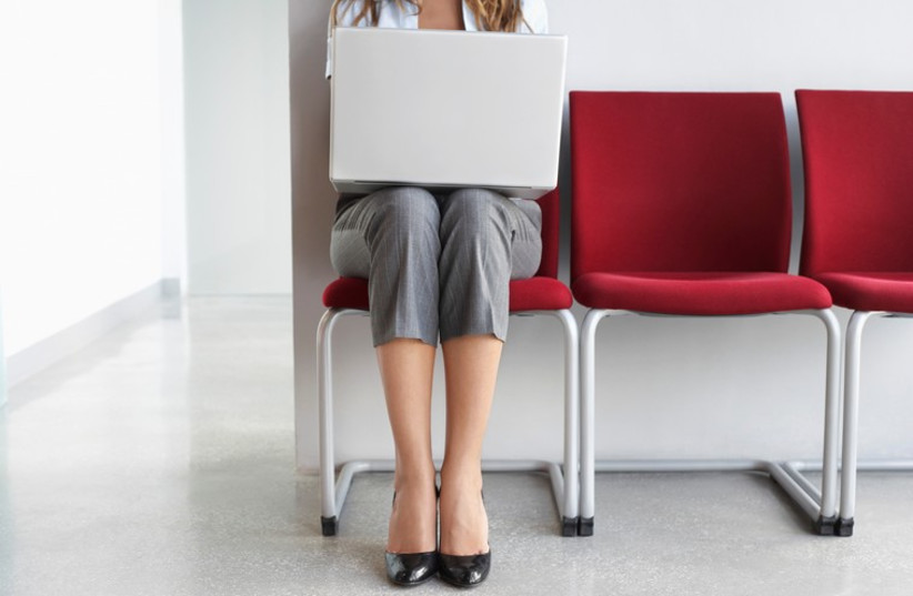 Woman using laptop in office corridor  (photo credit: ING IMAGE/ASAP)
