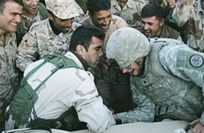 Iraqi US soldier arm wrestle 248.88 (photo credit: AP)