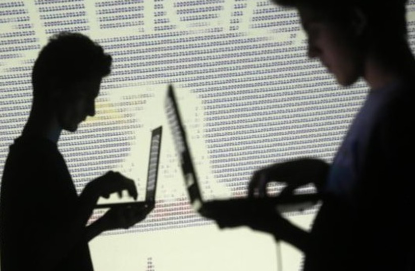 People are silhouetted as they pose with laptops in front of a screen projected with binary code and a Central Inteligence Agency (CIA) emblem (photo credit: REUTERS)