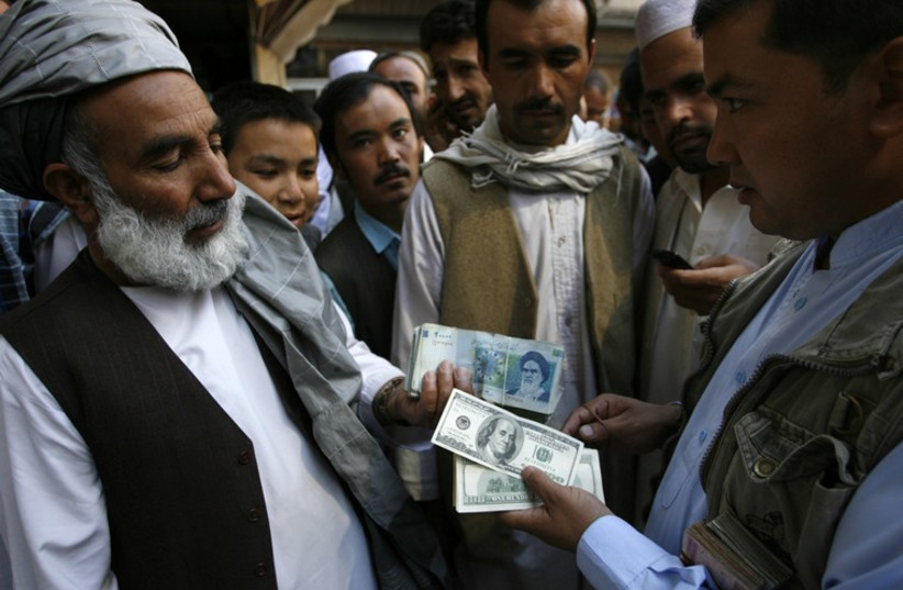 Afghan money lenders trade Iranian rial for dollars (photo credit: REUTERS)