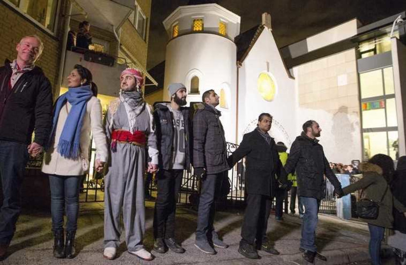 Muslims join hands to form a human shield as they stand outside a synagogue in Oslo (photo credit: REUTERS)