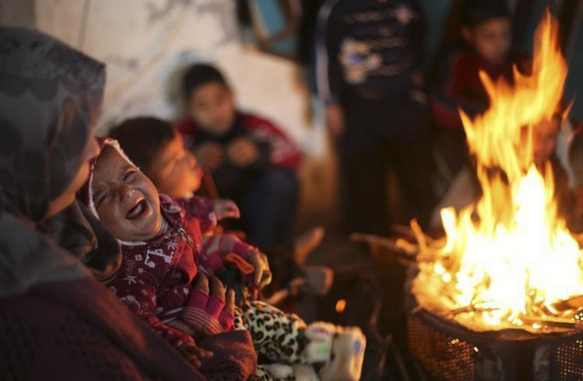 Members of a Palestinian family warm themselves by a fire at the remains of their house that witnesses said was destroyed by Israeli shelling (photo credit: REUTERS)