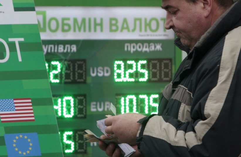 Man counts money near currency exchange in Kiev [file] (photo credit: REUTERS)
