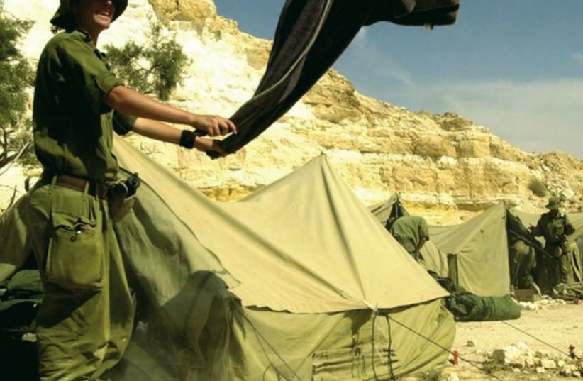 A female IDF soldier shaking out a blanket during a week-long survival course for women in the infantry at an undisclosed location in Israel (photo credit: REUTERS)
