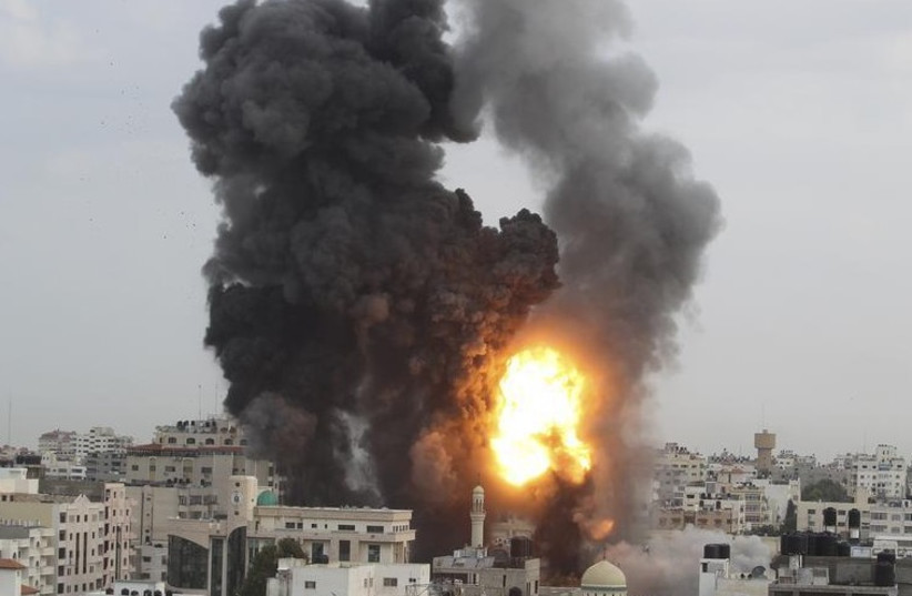 An explosion and smoke are seen after Israeli strikes in Gaza City (photo credit: REUTERS)