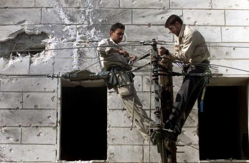 Palestinian electricians repair electric cables. (photo credit: REUTERS)