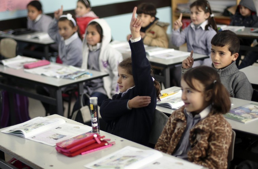 Palestinian first-graders sit with their schoolbooks during class in the West Bank city of Ramallah February 4, 2013. (photo credit: REUTERS)