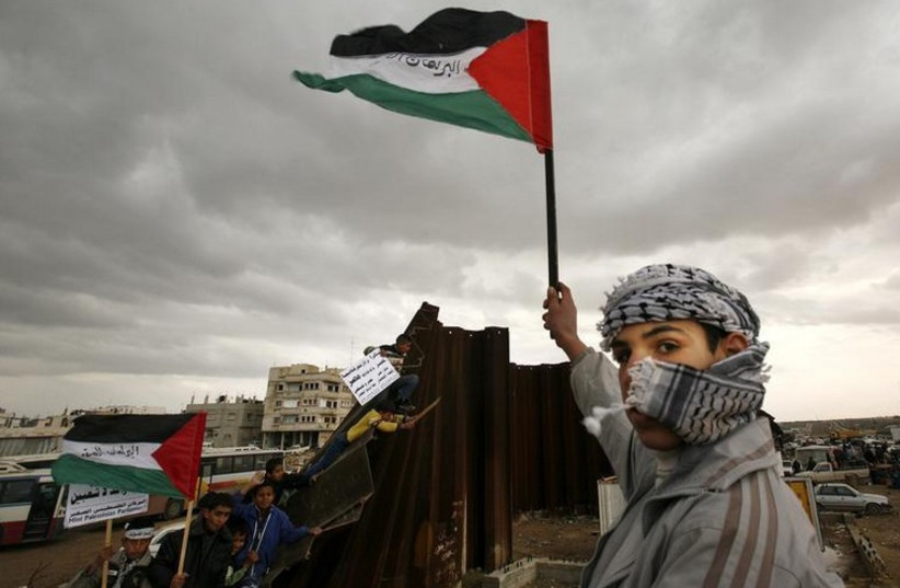 A Palestinian waves a flag near a destroyed section of the border wall between the Gaza Strip and Egypt (photo credit: REUTERS)