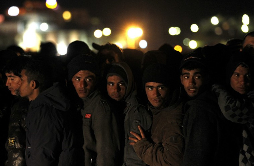 Migrants wait at Italian checkpoint prior to processing  (photo credit: REUTERS)