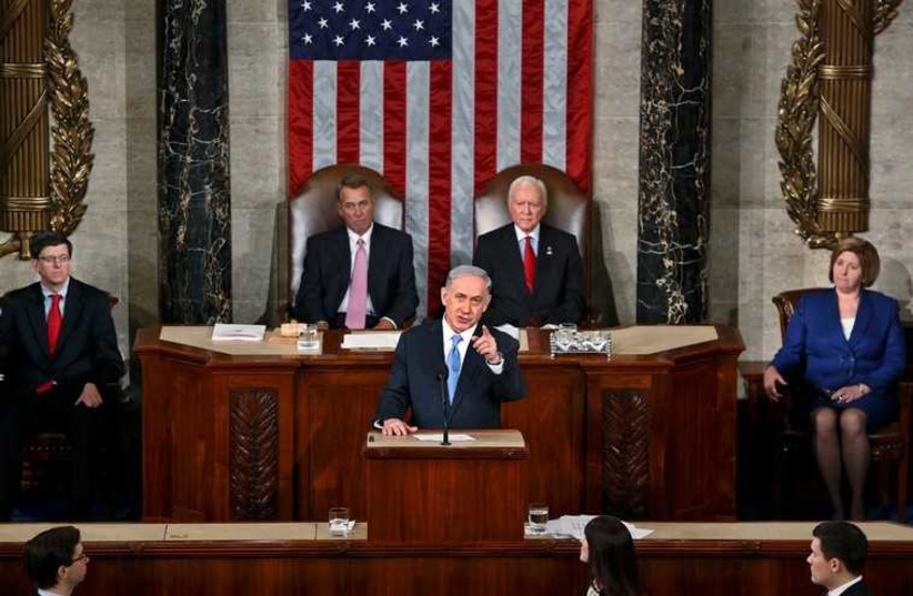 Prime Minister Benjamin Netanyahu during his speech to US Congress on March 3, 2015, with US Speaker of the House John Boehner and President pro tempore of the US Senate Orrin Hatch applauding behind him (photo credit: REUTERS)