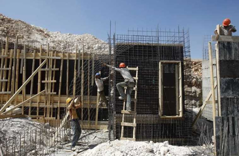Palestinian laborers work at a construction site in a settlement near Jerusalem  (photo credit: REUTERS)