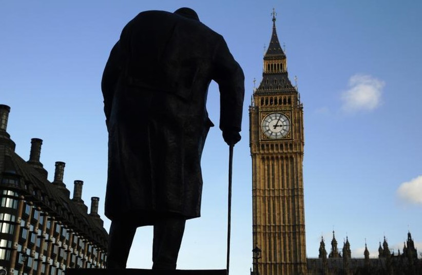 The statue of Britain's former Prime Minister Winston Churchill is silhouetted in front of the Houses of Parliament in London (photo credit: REUTERS)