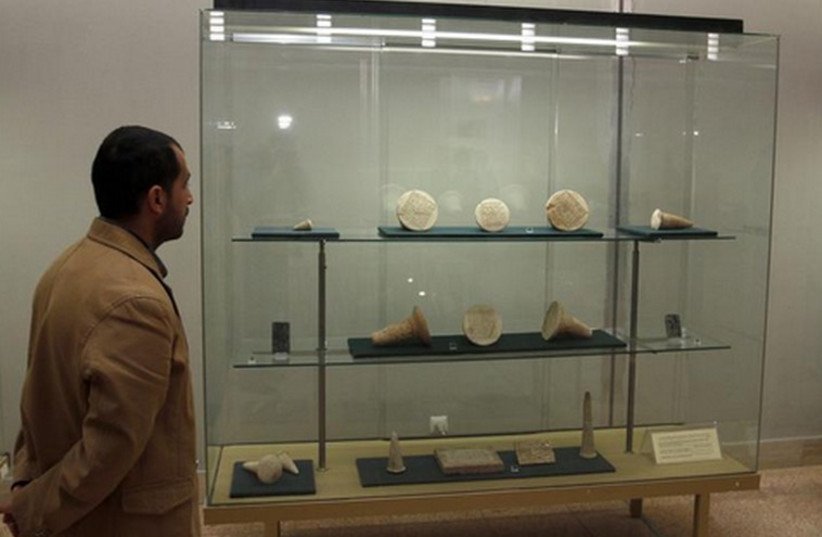A man looks at artifacts displayed inside the Iraqi National Museum in Baghdad (photo credit: REUTERS)
