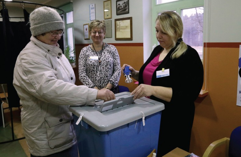 An Estonian citizen casts her vote during a parliamentary election in Uulu (photo credit: REUTERS)