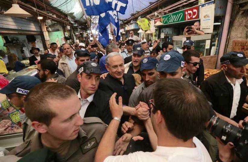 Prime Minister Benjamin Netanyahu trying to take a shuk stroll through Mahane Yehuda market on March 9, 2015 (photo credit: MARC ISRAEL SELLEM/THE JERUSALEM POST)