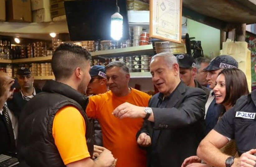 Prime Minister Benjamin Netanyahu making a purchase during his surprise visit to Mahane Yehuda market on March 9, 2015 (photo credit: MARC ISRAEL SELLEM/THE JERUSALEM POST)