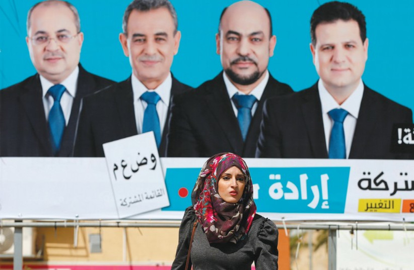 A WOMAN walks past a campaign billboard for the Joint (Arab) List in Umm el-Fahm yesterday (photo credit: REUTERS)