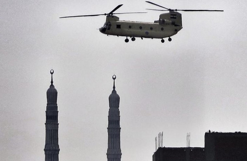 An army helicopter flies over a mosque in Cairo (photo credit: REUTERS)